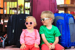 Kids sitting on suitcases ready to travel Stock Photos