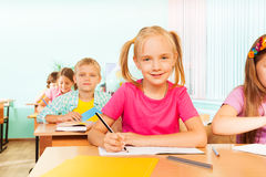 Kids sitting at table in classroom and writing. In exercise book during lesson Royalty Free Stock Photos