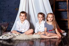 Kids sitting together boys girls brothers sisters look blue eyes next sit white trio three floor play up watch attic loft stock photos
