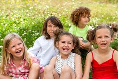 Kids sitting together in field. Royalty Free Stock Photography
