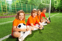 Kids sitting together on field near woodwork Stock Images