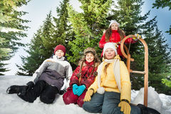 Kids sitting together outside near wooden sledge Royalty Free Stock Photo