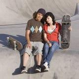 Kids at skatepark. Teen couple hangs out at skatepark Stock Photo
