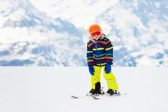 Kids ski. Winter family snow sport. Child skiing. Child skiing in the mountains. Kid in ski school. Winter sport for kids. Family Christmas vacation in the Alps stock image