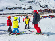 Kids skiing in an Austria ski school. ZURS, AUSTRIA - APRIL 10, 2015: Kids skiing in a the Zurs - Lech, Arlberg, ski school. Parents and spectators are watching Stock Photography
