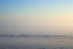 Kids are skiing on the frozen lake. Winter, frozen lake, children are skiing, mist Stock Image