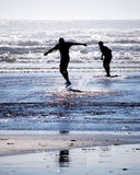 Kids Skim Boarding. Two kids silhouetted in the afternoon sun on the beach playing in the waves with skim boards which are similar to surf boards Royalty Free Stock Photos