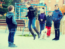 Kids skipping on chinese jumping elastic rope in yard Royalty Free Stock Photos