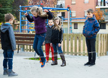 Kids skipping on chinese jumping elastic rope in yard Stock Photography