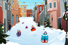 Kids Sledding on a Snowy Street During Winter Season Stock Photography