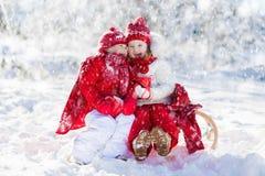 Kids sledding in winter forest. Children drink hot cocoa in snow. Kids sledding in winter forest. Children drink hot chocolate on sled under warm blanket. Boy Royalty Free Stock Photo