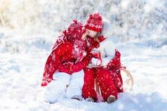 Kids sledding in winter forest. Children drink hot cocoa in snow. Kids sledding in winter forest. Children drink hot chocolate on sled under warm blanket. Boy Stock Images