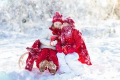 Kids sledding in winter forest. Children drink hot cocoa in snow. Kids sledding in winter forest. Children drink hot chocolate on sled under warm blanket. Boy Royalty Free Stock Image