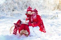 Kids sledding in winter forest. Children drink hot cocoa in snow. Kids sledding in winter forest. Children drink hot chocolate on sled under warm blanket. Boy Royalty Free Stock Image