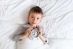 Free Kids Sleeping Concept With Asleep Little Boy In Bed With Alarm Clock Stock Photos - 138984033