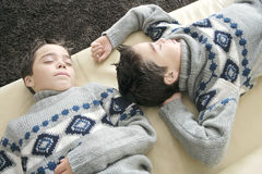 Kids sleeping on couch. Two identical twin brothers sleeping on a sofa in the living room Stock Image