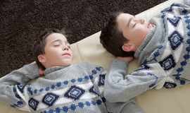 Kids sleeping on couch. Two identical twin brothers sleeping on a white leather couch wihle wearing identical jumpers Royalty Free Stock Images