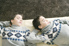Kids sleeping on couch. Overhead view of two identical twin brothers sleeping on a sofa in the living room Stock Image