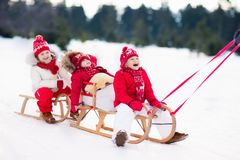 Kids on sleigh. Children sled. Winter snow fun. Little girl and boy enjoy a sleigh ride. Child sledding. Toddler kid riding a sledge. Children play outdoors in Royalty Free Stock Image