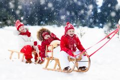 Kids on sleigh. Children sled. Winter snow fun. Little girl and boy enjoy a sleigh ride. Child sledding. Toddler kid riding a sledge. Children play outdoors in Royalty Free Stock Photos