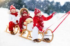 Kids on sleigh. Children sled. Winter snow fun. Little girl and boy enjoy a sleigh ride. Child sledding. Toddler kid riding a sledge. Children play outdoors in Stock Image