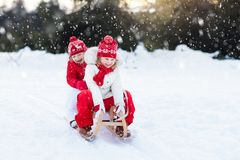 Kids on sleigh. Children sled. Winter snow fun. Little girl and boy enjoy a sleigh ride. Child sledding. Toddler kid riding a sledge. Children play outdoors in stock photography