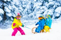 Kids on sleigh ride. Children sledding. Winter snow fun. Little girl and boy enjoy a sleigh ride. Child sledding. Toddler kid riding a sledge. Children play Stock Images