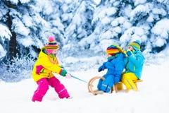Kids on sleigh ride. Children sledding. Winter snow fun. Little girl and boy enjoy a sleigh ride. Child sledding. Toddler kid riding a sledge. Children play stock images