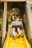 Kids on slide. Hispanic girl hugging boy on top of slide smiling at viewer royalty free stock photos