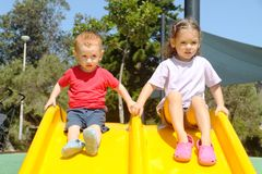 Kids on slide. Two kids on plastic yellow slide Stock Photos