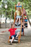 Kids sliding down together on playground's construction Royalty Free Stock Photos