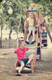 Kids sliding down together on playground`s construction Royalty Free Stock Photos