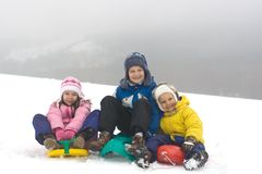 Kids Sliding on Fresh Snow. Three children sit on their downhill sleds, ready to have fun in fresh snow on a cold, wintry day Royalty Free Stock Image