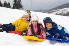 Kids Sliding on Fresh Snow. Three children, laying on their downhill sleds, stop to pose for this picture in the snow on a cold, wintry day Royalty Free Stock Photos