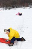 Kids Sliding in Fresh Snow. Two children out in the snow on a cloudy day, having fun downhill sliding Royalty Free Stock Photos