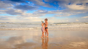 Kids Small Girl with Pigtail Boy Stand in Shallow Waves on Beach. Two blond kids small girl with pigtail and boy stand in running shallow waves on beach against stock footage