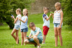 Kids with smartphones playing game in summer park Royalty Free Stock Images