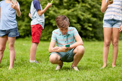 Kids with smartphones playing game in summer park Stock Images
