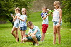 Kids with smartphones playing game in summer park Stock Image