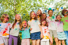 Kids smeared with colored powder standing in a row Stock Photography