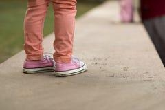 Kids sneakers walking on street Stock Photos