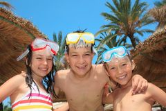 Kids with snorkel masks. Three kids with snorkel masks and bathing suits Royalty Free Stock Photography