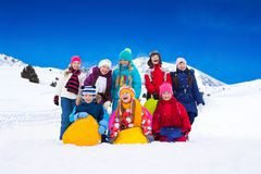 Kids and snow. Group of happy boys and girls some with sled, standing together in snow royalty free stock image