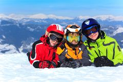 Kids in snow on mountaintop. Three children wearing colorful ski clothing, lying in snow on a mountaintop in the Alps Royalty Free Stock Photos