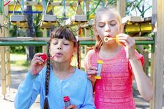 Kids with soap bubbles. Kids blowing soap bubbles on a playground Royalty Free Stock Photos