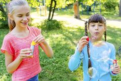 Kids with soap bubbles. Kids blowing soap bubbles on a playground Stock Photo