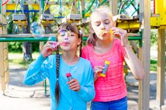Kids with soap bubbles. Kids blowing soap bubbles on a playground Royalty Free Stock Image