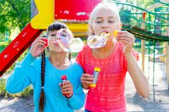 Kids with soap bubbles. Kids blowing soap bubbles on a playground Royalty Free Stock Photography
