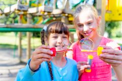 Kids with soap bubbles. Kids blowing soap bubbles on a playground Royalty Free Stock Photo