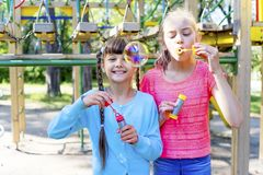 Kids with soap bubbles. Kids blowing soap bubbles on a playground Stock Images